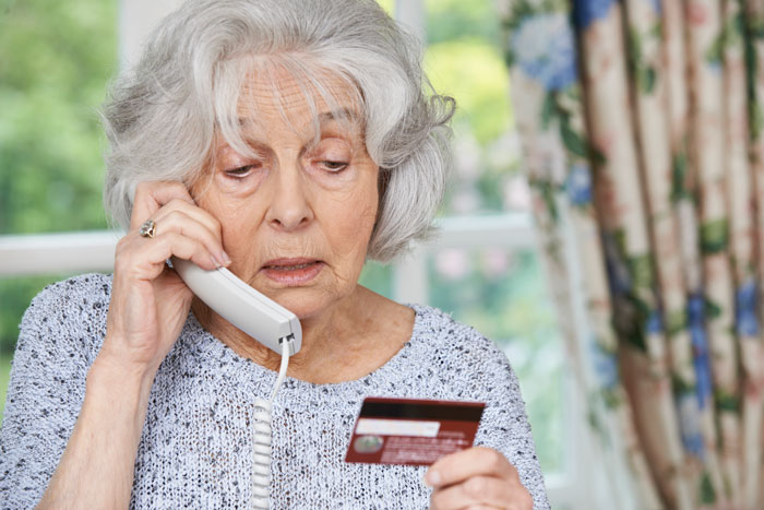 senior woman giving credit card details over the phone