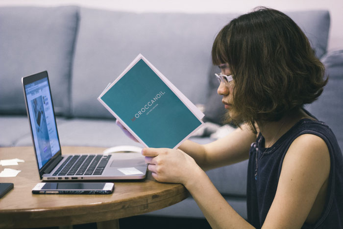 young asian woman student researching online and with book